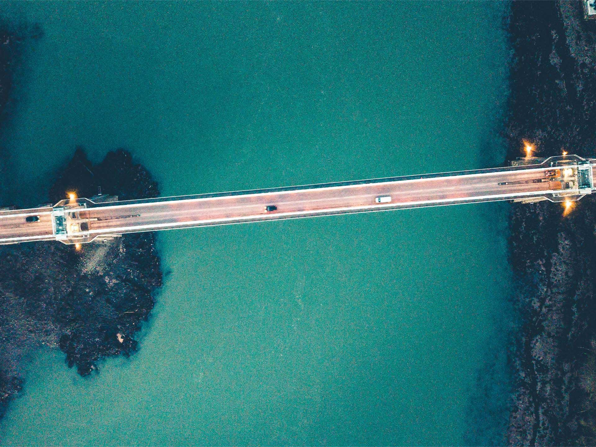 Drrone captured shot of Menai Bridge from above as cars cross over.