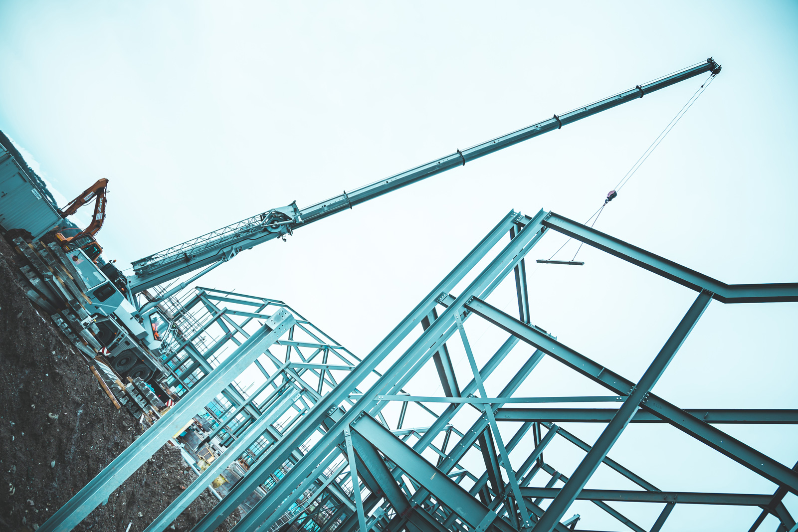 Crane carryingn a steel beam in the process of constructing Madoc Cove Apartments steel frame
